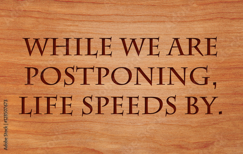 Fotografie, Obraz  While we are postponing, life speeds by - quote on wooden red oak background