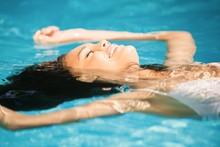 Beautiful Woman Floating In Pool