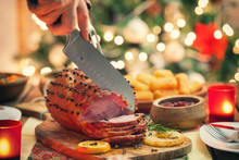 Young Woman Carving Glazed Holiday Ham