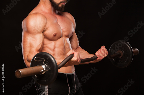 Fotografie, Obraz  Muscular male athlete is training by lifting the barbell