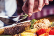 canvas print picture - Chef in hotel or restaurant kitchen cooking only hands. Prepared beef steak with vegetable decoration.