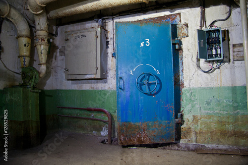 Photo  Blue rusty hermetical door of old abandoned Soviet bomb shelter