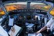 Airplane cockpit flying on colorful Waimea Canyon State Park, also called Grand Canyon of Pacific, at sunset in Kauai, Hawaii, United States, with pilots arms and blank white papers for copy space.