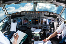 Airplane Cockpit Flying In A Cloudy Blue Sky At Day. With Pilots Arms And Blank White Papers For Copy Space.