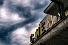 Old Abandoned Closed Movie Theater Under Stormy Sky