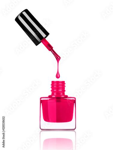 Fotografie, Obraz  Nail polish dripping from brush into bottle on white background