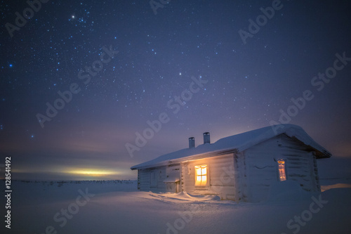 Night sky over snowcapped hut