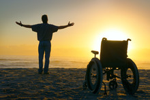 Miracle Spiritual Healing Crippled Man Exalted Arms Spread At The Ocean Shoreline As He Stands Up Out Of His Wheelchair And Walks Towards The Sunrise