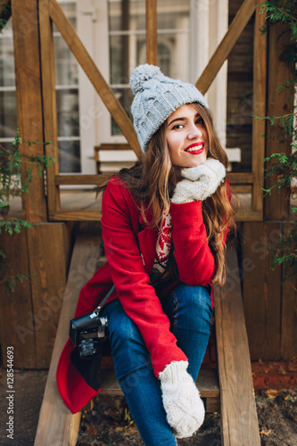 6d8688766f9b0 Pretty brunette girl in red coat, knitted hat and white gloves sitting on  wooden stairs outdoor. She has long hair, smiling to camera. By Look!
