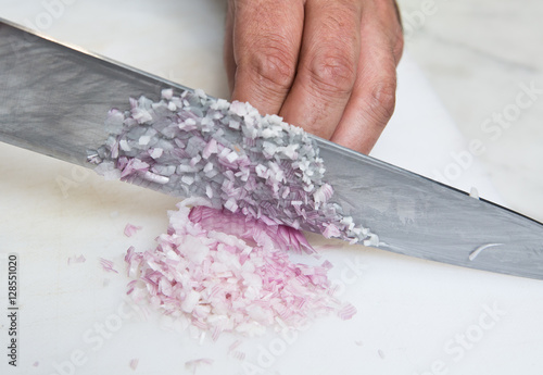 Fotomural  A knife dicing fresh organic Shallots, on a white cutting board.