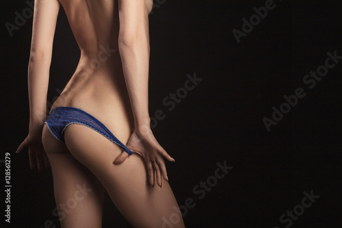 Zdjęcie XXL rozbieranie majtek z tan szczupłe ciało kobiece na czarnym tle z lato