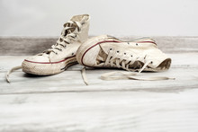 Old White Sneakers On Wooden Background