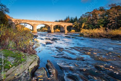 Foto auf Leinwand Bridges Bywell Bridge crosses River Tyne, as it flows through Northumberland, under the stone arched Bywell Road Bridge near Stocksfield