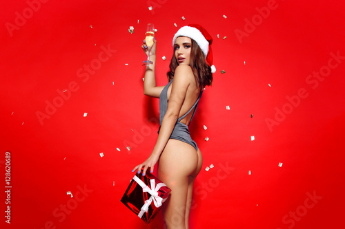 ea3057264 beautiful young girl model stands on red background in sexy bathing suit  bikini and a Christmas