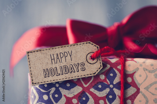 gift with a label with the text happy holidays Poster