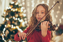 Young Girl Playing Violin In Front Of Christmas Tree