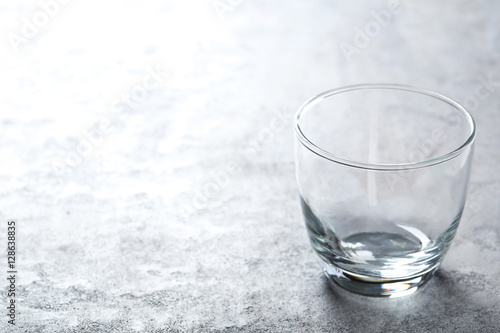 Foto op Canvas Alcohol Empty glass on a grey wooden table