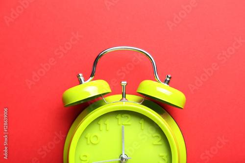 Fotografía  Green alarm clock on a red background