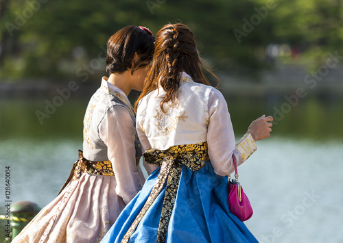 Fotobehang Seoel Two Korean girl dressed in old traditional dress talking at the lake in a park