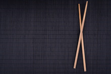 Crossed Chopsticks On Black Bamboo Mat, Overhead, Background, Flat Lay, Overhead