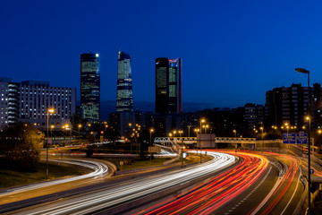 Anochecer de Madrid con los rascacielos y las luces de la carretera