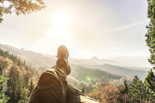 Valokuva  Man is enjoying the scenery on the mountain top. Pov view.