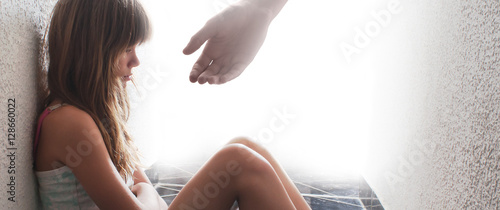 Obraz Sad teenage girl sitting on the floor while hand is offering help - fototapety do salonu