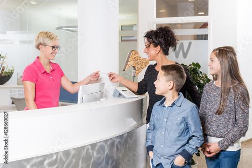 Fotografie, Obraz  Mutter mit Kindern beim Zahnarzt, gibt Versichertenkarte ab