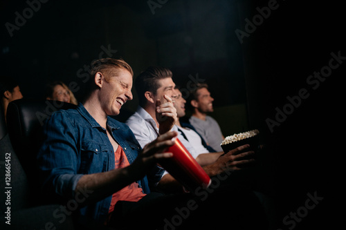 Fotografija  Young man with friends watching comedy movie