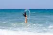 Tanned brunette in white bikini enjoying summer on the beach
