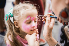 Woman Painting Face Of Kid Out...