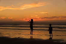Children Playing In The Surf At Sunset, Pismo Beach California