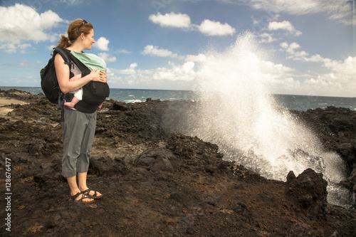 A woman in her thirties carrying an infant hikes past a blowhole next to the Pacific Ocean.