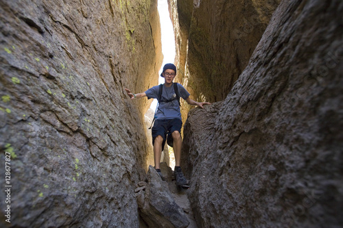 Young man climbs the Catacombs along the Owens River Gorge. Poster