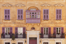 Front View Of A Medieval Mediterranean Style Building With Purple Balcony, Windows And Shutters
