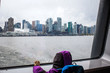VANCOUVER, BRITISH COLUMBIA, CANADA. A small child looks through the rain-covered window of a ferry boat with downtown skyline in distance across water.