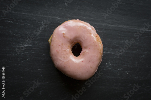 A donut sits on a cutting stone. Poster