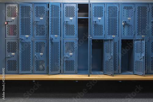 Fotografia, Obraz Blue metal cage lockers in a locker room with some doors open and some closed wi