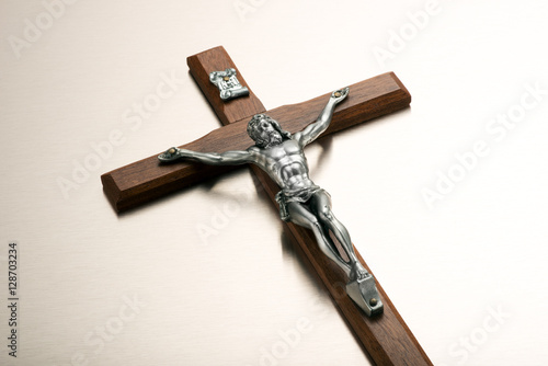 Fotografering Silver metal Christ on a wooden crucifix