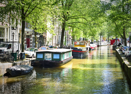 Foto op Aluminium Amsterdam Canal of Amsterdam, Amstel river with houseboats and green trees, idyllic scene.