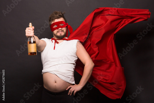 Valokuva  Super anti hero man showing bottle with wine or whiskey while drinking alcohol isolated on black background
