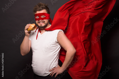 Valokuva  Super hero glutton man eating hanburger isolated on black