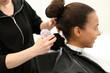 Pędzel fryzjerski. Fryzjer omiata z włosów ramiona klientki