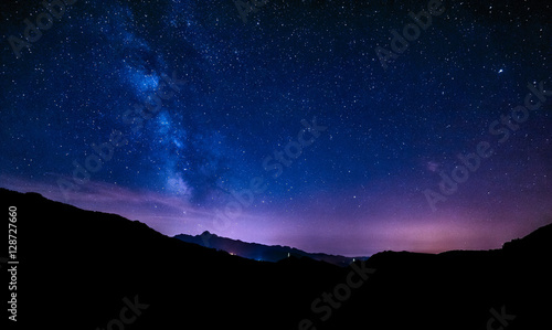 Poster de jardin Nuit night sky stars milky way blue purple sky in starry night over mountains