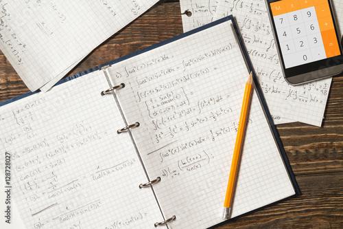 Mathematical equations written in a notebook. Calculator app.