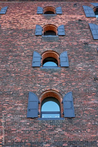 Several arched windows with shutters, fastened to a brick facade of a former ind Poster