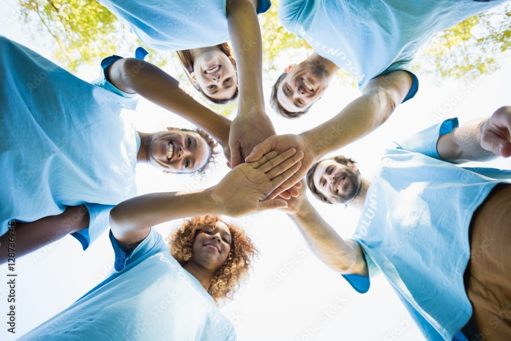 Fototapeta Group of volunteer forming huddles
