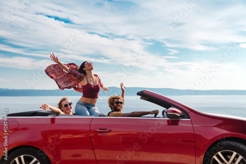 Group of happy young people waving from the red convertible. - 128746852