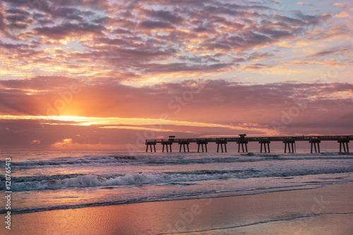 Fotografie, Obraz  Sun rising over horizon and pier, beach illuminated with sunlight, beautiful sky reflected on the beach