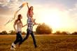 Leinwandbild Motiv familie mit tochter rennt und lässt drachen steigen